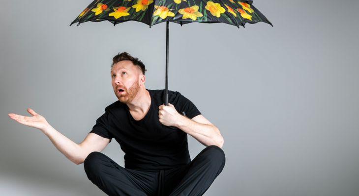 Jason Byrne holding a umbrella