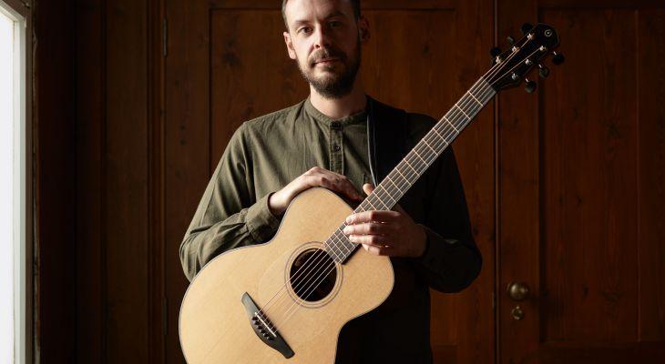 Sam Carter holding a guitar